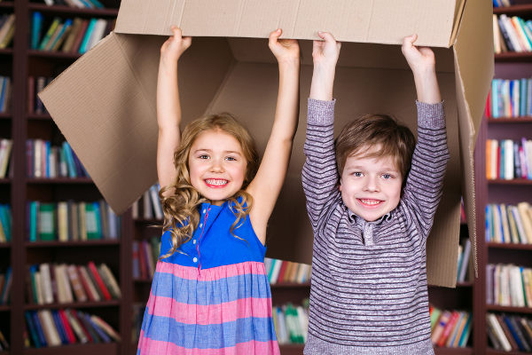 kids holding box overhead